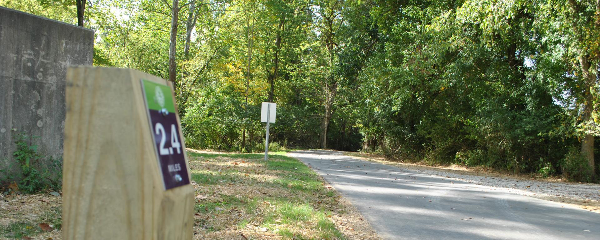 mile marker next to a paved trail