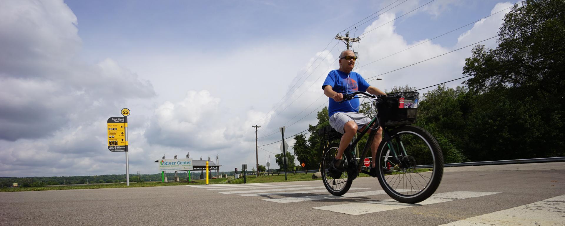 man riding bike across a street